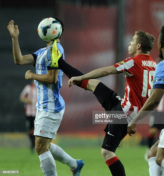 Athletic Bilbao's forward Iker Muniain vies with Malaga's forward Juanmi during the Spanish league football match Athletic Club Bilbao vs Malaga CF...