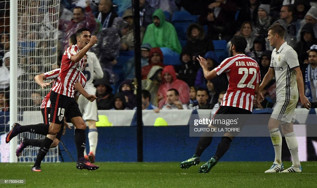 Athletic Bilbao's forward Sabin Merino (L) celebrates a goal with Athletic's midfielder Raul Garcia (2nd R) during the Spanish league football match between Real Madrid CF and Athletic Club Bilbao at the Santiago Bernabeu stadium in Madrid on October 23, 2016. / AFP / CURTO