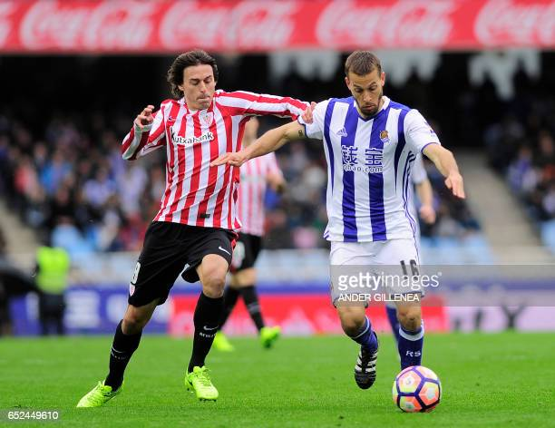 Athletic Bilbao's midfielder Ander Iturraspe vies with Real Sociedad's midfielder Sergio Canales during the Spanish league football match Real...