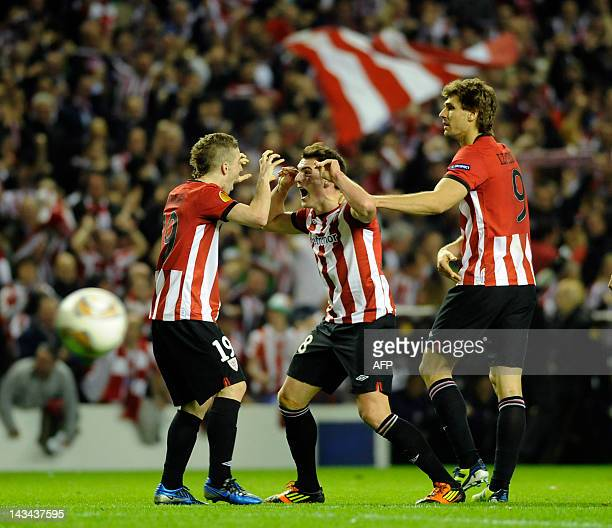 Athletic Bilbao's midfielder Ibai Gomez celebrates with teammates forward Iker Muniain and forward Fernando Llorente after scoring during the UEFA...