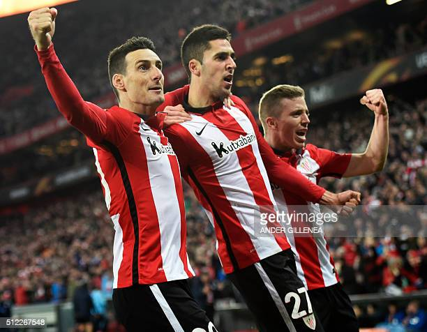 Athletic Bilbao's midfielder Sabin Merino celebrates with teammates forward Aritz Aduriz and forward Iker Muniain after scoring during the UEFA...
