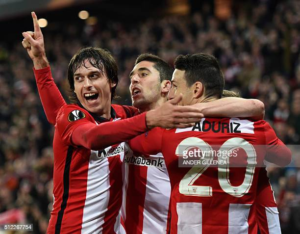 Athletic Bilbao's midfielder Sabin Merino celebrates with teammates forward Aritz Aduriz and midfielder Ander Iturraspe after scoring during the UEFA...