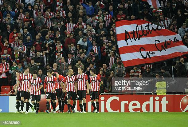Athletic Bilbao's players celebrate after scoring as a supporter waves the club's flag reading we are Athletic during the UEFA Champions League Group...