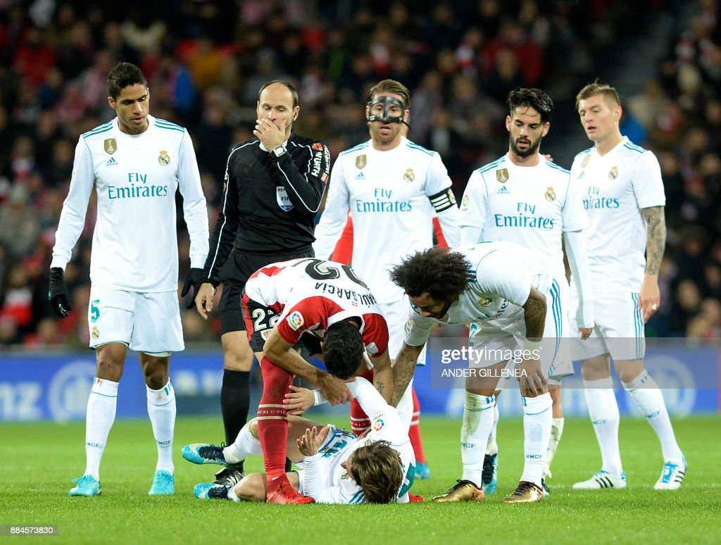 Athletic Bilbao's Raul Garcia Escuedro checks on Real Madrid's Croatian midfielder Luka Modric after a fall during the Spanish league football match Athletic Club Bilbao vs Real Madrid CF at the San Mames stadium in Bilbao on December 2, 2017. /