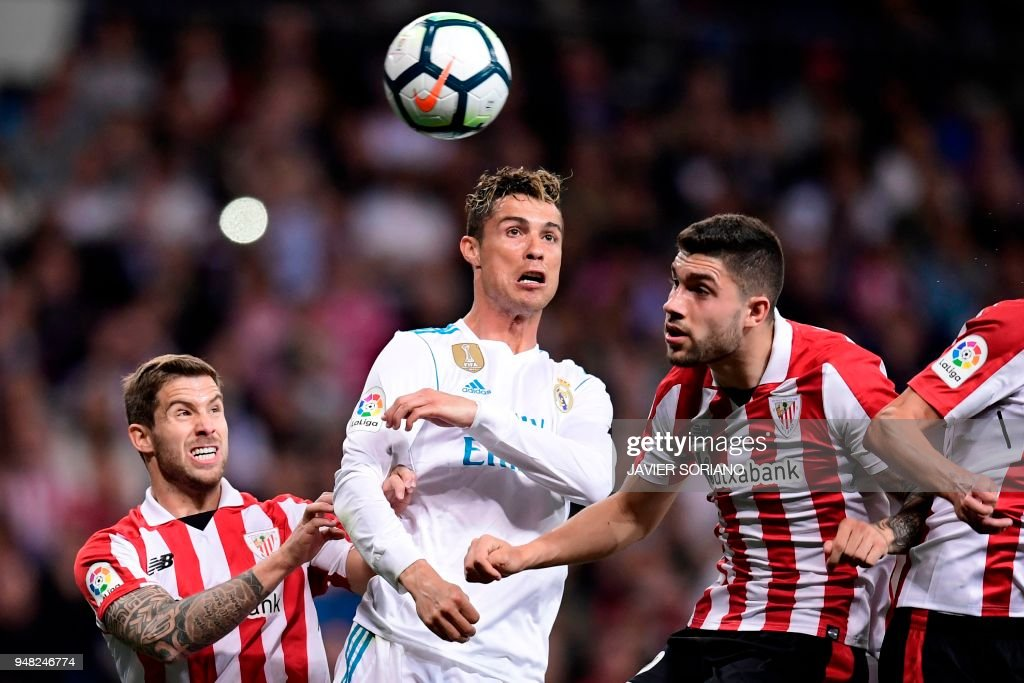 TOPSHOT - Athletic Bilbao's Spanish defender Inigo Martinez (L) and Athletic Bilbao's Spanish defender Unai Nunez (R) vie with Real Madrid's Portuguese forward Cristiano Ronaldo (C) during the Spanish league football match Real Madrid CF against Athletic Club Bilbao at the Santiago Bernabeu stadium in Madrid on April 18, 2018.