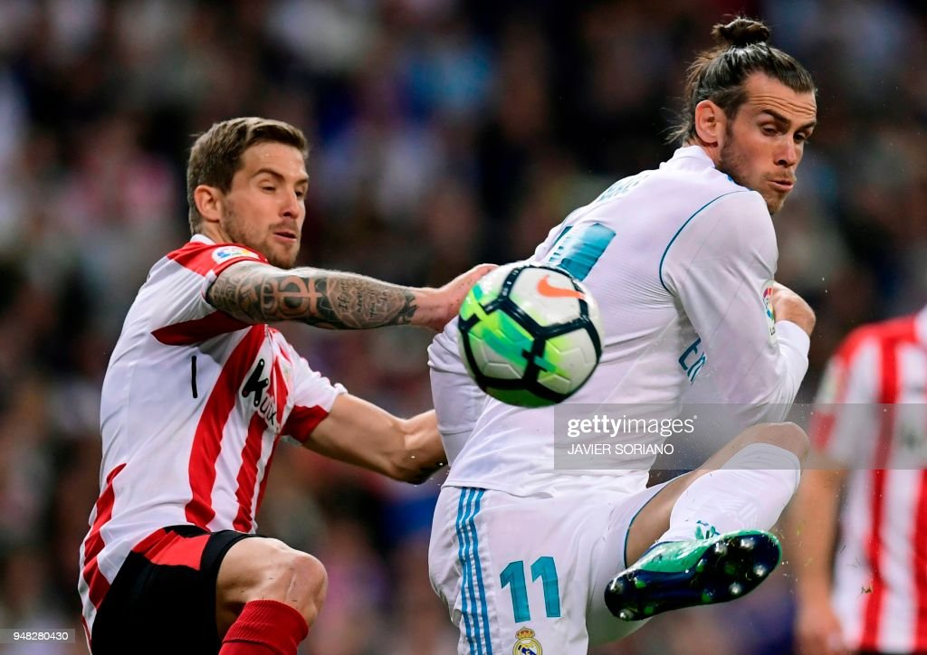 Athletic Bilbao's Spanish defender Inigo Martinez (L) vies with Real Madrid's Welsh forward Gareth Bale during the Spanish league football match Real Madrid CF against Athletic Club Bilbao at the Santiago Bernabeu stadium in adrid on April 18, 2018. /
