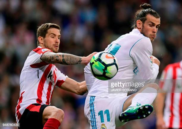 Athletic Bilbao's Spanish defender Inigo Martinez vies with Real Madrid's Welsh forward Gareth Bale during the Spanish league football match Real...