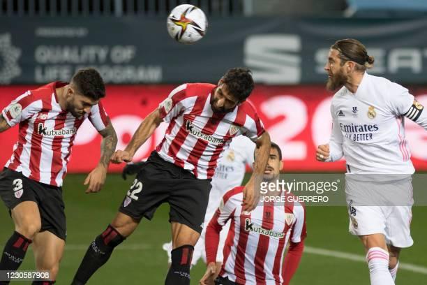 Athletic Bilbao's Spanish defender Unai Nunez and Spanish forward Raul Garcia jump for the ball next to Real Madrid's Spanish defender Sergio Ramos...