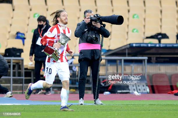 Athletic Bilbao's Spanish forward Iker Muniain runs with the winner's trophy as he celebrates after winning the Spanish Super Cup final football...