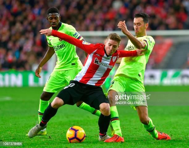 Athletic Bilbao's Spanish forward Iker Muniain vies with Barcelona's Spanish midfielder Sergio Busquets and Barcelona's French forward Ousmane...