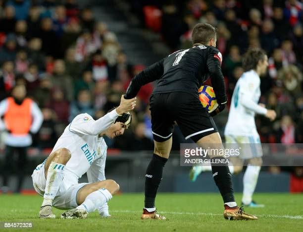 Athletic Bilbao's Spanish goalkeeper Kepa Arrizabalaga Revuelta helps Real Madrid's Portuguese forward Cristiano Ronaldo stand up during the Spanish...