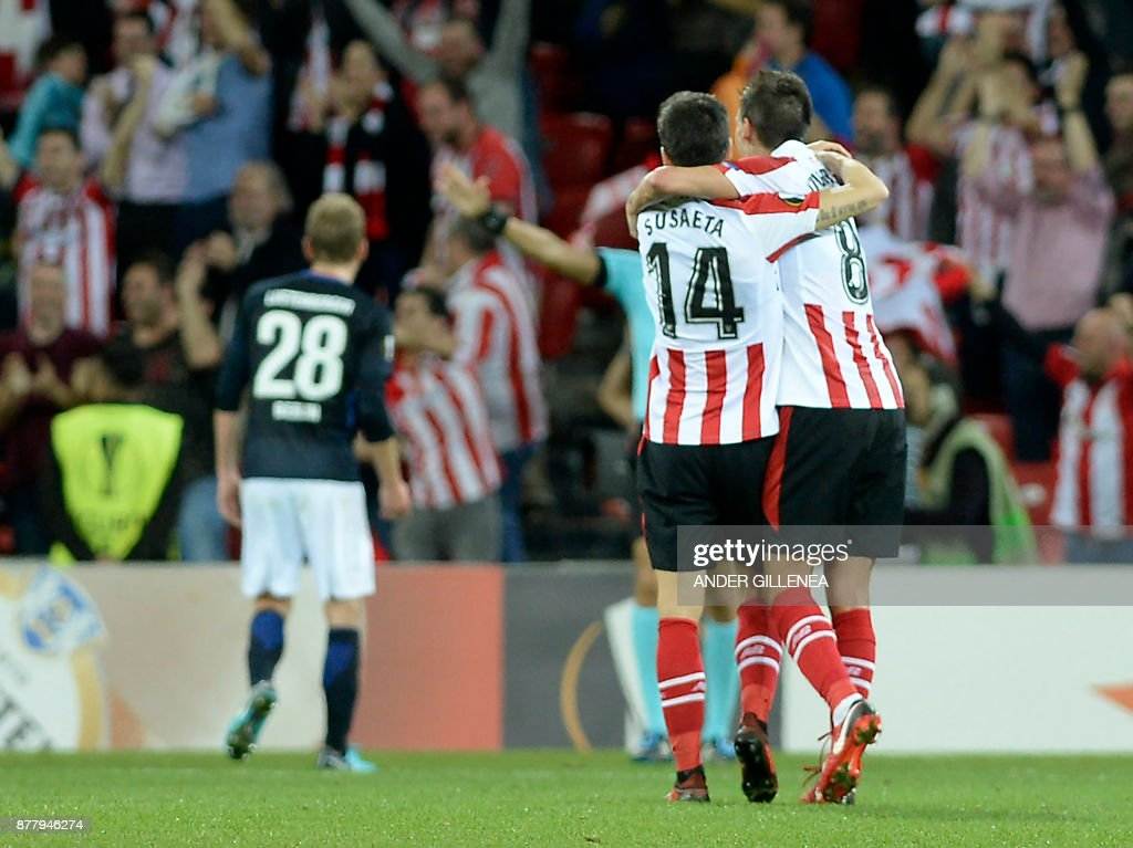 Athletic Bilbao's Spanish midfielder Markel Susaeta hugs Spanish midfielder Ander Iturraspe (R) as they celebrate their team's third goal during the Europa League football match Athletic Club Bilbao vs Hertha BSC Berlin at the San Mames stadium in Bilbao on November 23, 2017. /