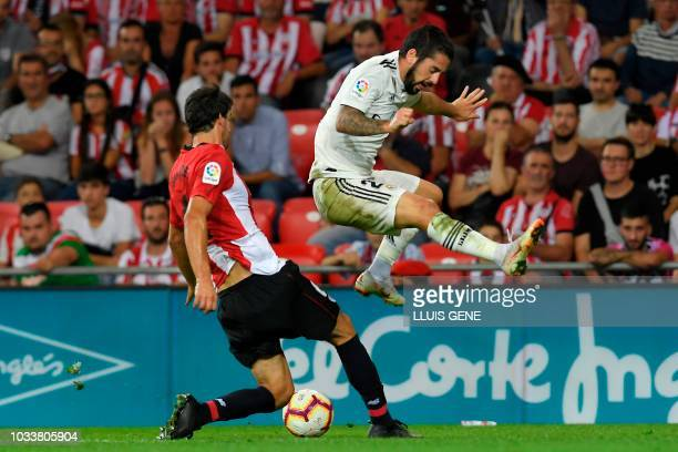 Athletic Bilbao's Spanish midfielder Mikel San Jose vies with Real Madrid's Spanish midfielder Isco during the Spanish league football match between...