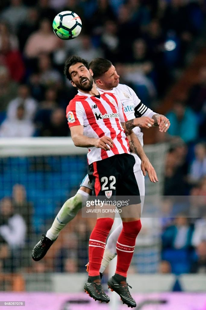 Athletic Bilbao's Spanish midfielder Raul Garcia (L) jumps for the ball with Real Madrid's Spanish defender Sergio Ramos during the Spanish league football match Real Madrid CF against Athletic Club Bilbao at the Santiago Bernabeu stadium in Madrid on April 18, 2018. /
