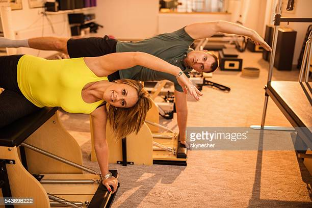 atlético casal fazendo exercícios de alongamento em máquinas de pilates. - reformista - fotografias e filmes do acervo