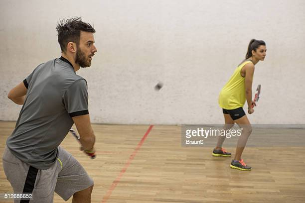 Athletic couple exercising racketball on a court.