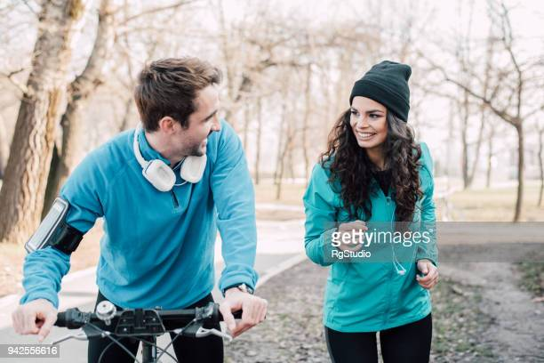 Athletic couple in the park riding a bicycle and running