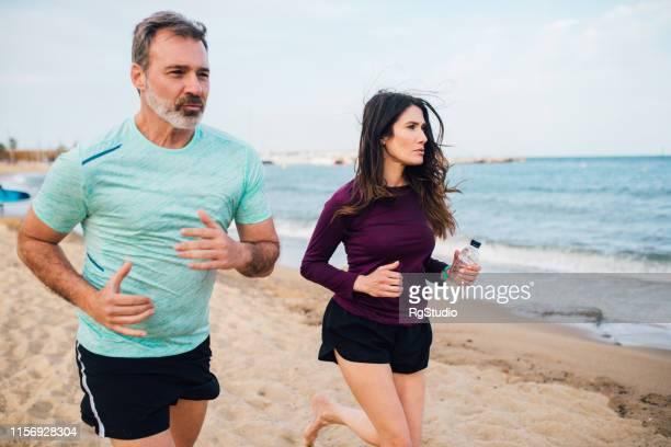 pareja atlética corriendo en la playa - pareja hombre mayor y mujer joven fotografías e imágenes de stock