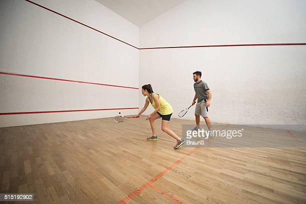 Athletic couple playing racketball on a court.