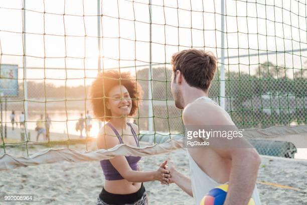 sportliche paar händeschütteln nach beach-volleyball - strand volleyball der männer stock-fotos und bilder