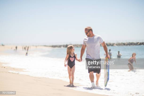Athletic dad plays with his girls at the beach on a sunny afternoon
