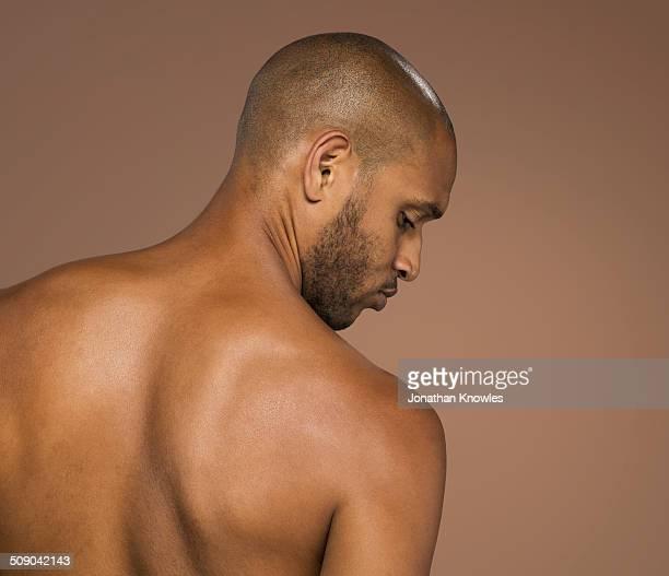 athletic dark skinned male looking over shoulder - naakte man en profiel stockfoto's en -beelden