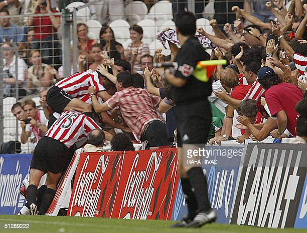 Athletic de Bilbao's players celebrate their first goal against Valencia with their supporters 11 September 2004 during a Spanish league football...