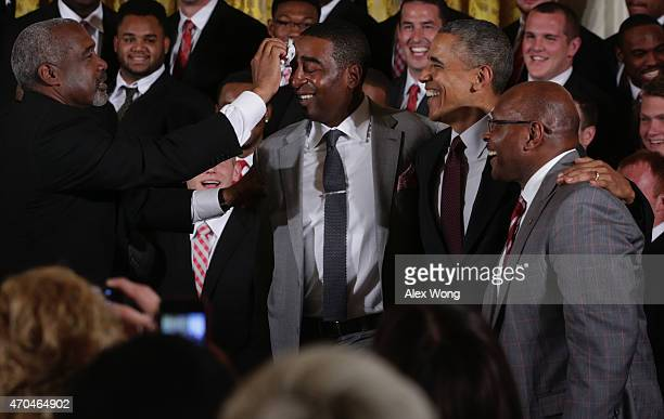Athletic Director Gene Smith of the Ohio State University Buckyes football team wipes the face of former team player Cris Carter as US President...