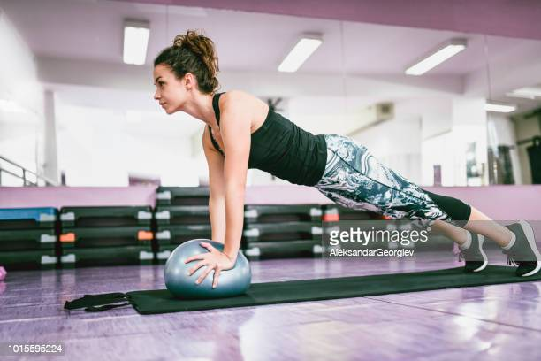 Athletic Female Doing A Plank Exercise On Fitness Ball In Gym