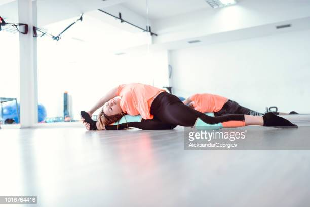 Athletic Female Doing Difficult Flexibility Exercise In Gym