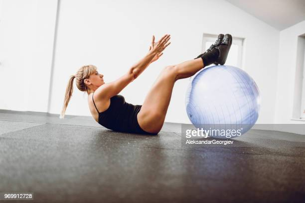 Athletic Female Doing Sit Ups In Gym With Fitness Ball