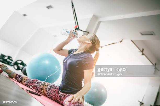 athletic female drinking water and listening to music while doing the splits - legs spread woman stock photos and pictures