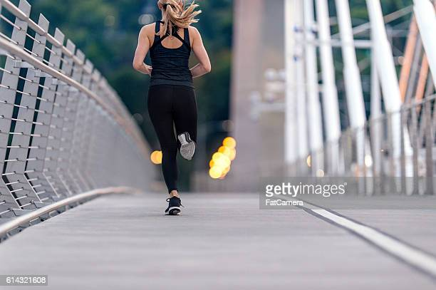 athletic female figure sprinting across a bridge - yoga pants stock photos and pictures