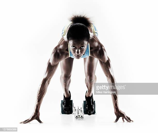 athletic female sprinter on starting blocks - muscular build stock pictures, royalty-free photos & images