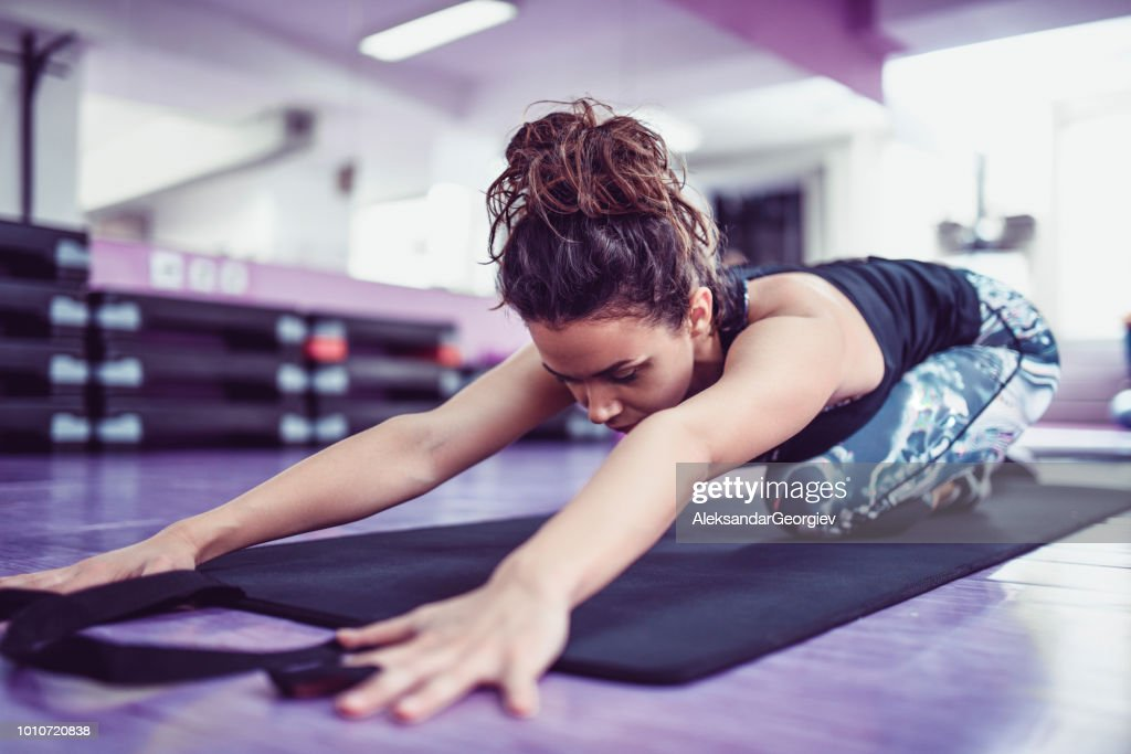 Athletic Female Stretching On Exercise Mat In Gym : Stock Photo