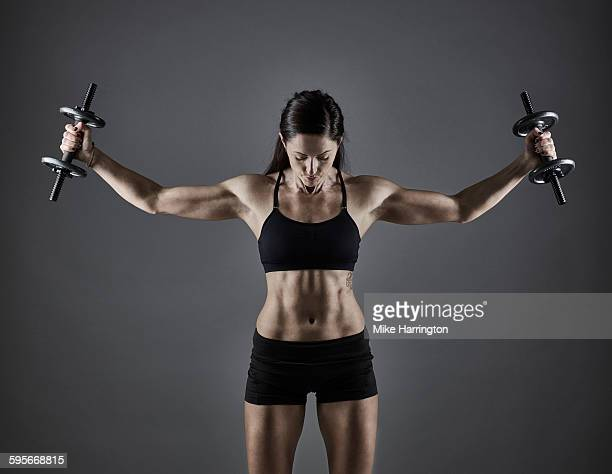 athletic female using dumbbells to tone muscles - erin james stock-fotos und bilder
