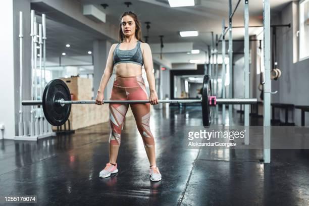 デッドリフト強度に取り組むアスレチック女性 - タイツ ストックフォトと画像