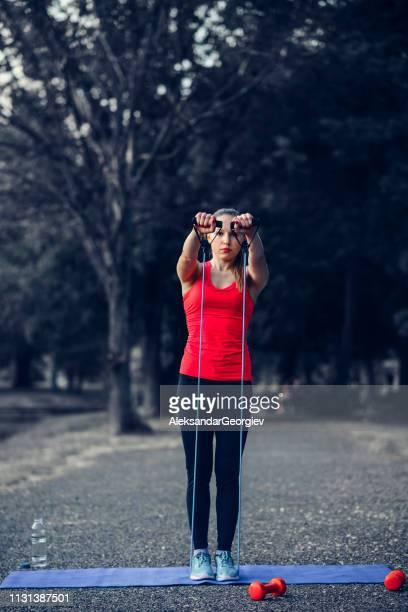 fêmea atlética que trabalha para fora com corda no parque - flexibilidade - fotografias e filmes do acervo