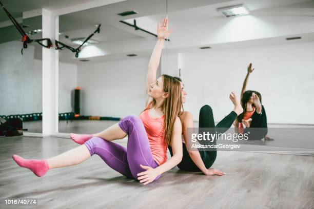 Athletic Females Practicing Yoga Positions In Gym Near Mirror