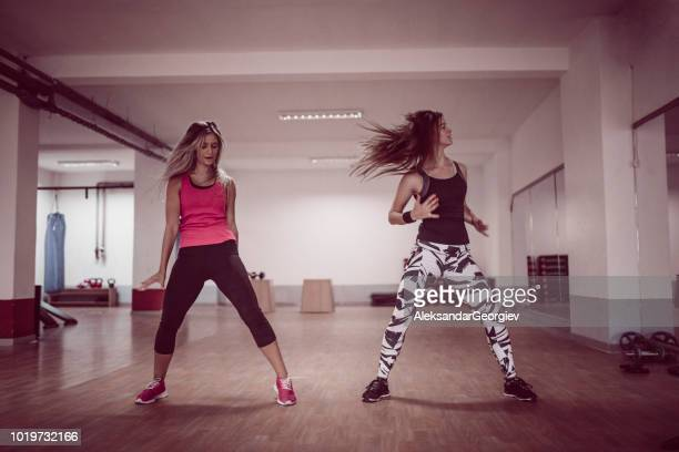 athletic females working out with zumba dancing exercises in gym - rumba stock photos and pictures