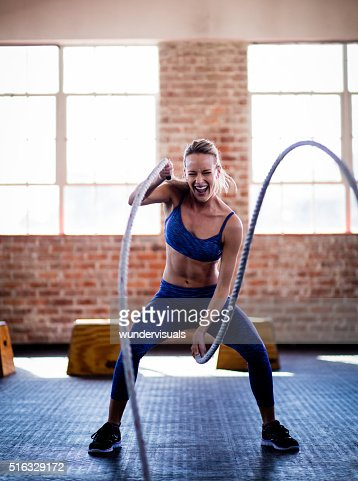 Athletic Girl Efforting On Gym Training With Ropes At Gym