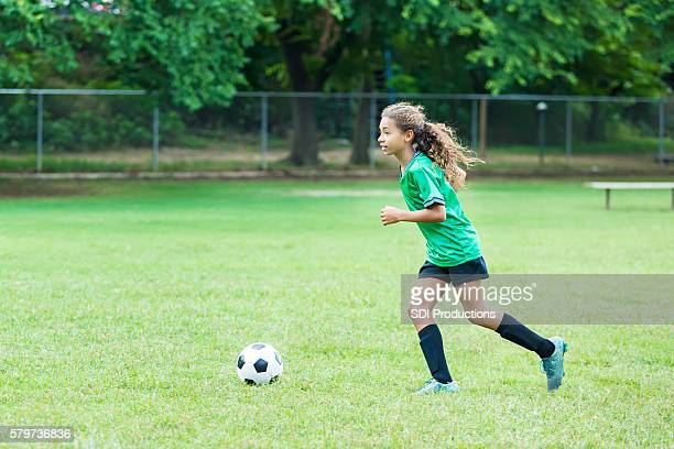 Athletic girl playing soccer and running on the field