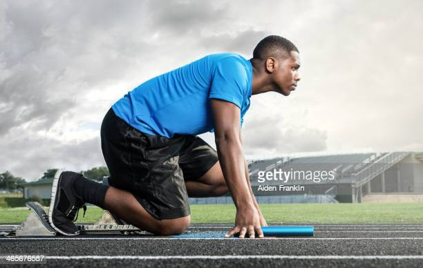 Athletic High School Track Star on Starting Block Before Race