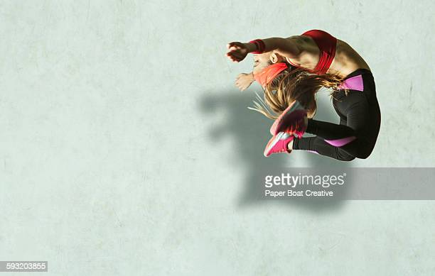 Athletic lady in sports wear jumping high