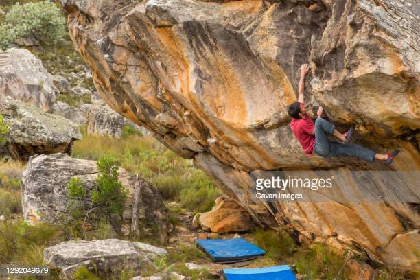 athletic male climbs outside on a boulder above crash pads - bedrock stock pictures, royalty-free photos & images