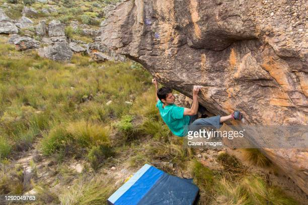 athletic male climbs outside on a boulder in a grassy field - bedrock stock pictures, royalty-free photos & images