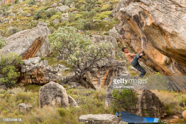 athletic male climbs outside on a boulder in a grassy, rocky landscape - bedrock stock pictures, royalty-free photos & images