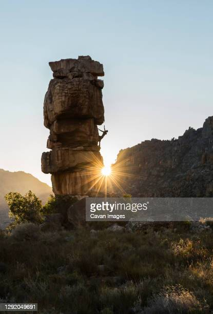 athletic male climbs outside on a boulder with sun rays - bedrock stock pictures, royalty-free photos & images