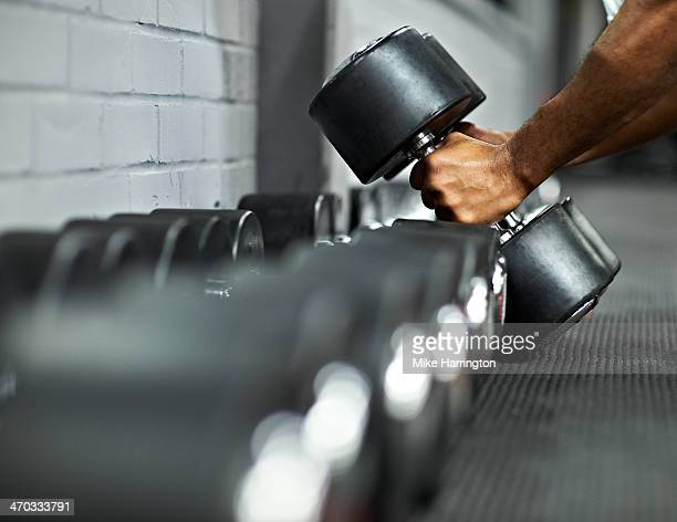athletic male picking up dumbbells in gym - dumbbell stock pictures, royalty-free photos & images