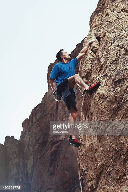 Athletic Male Rock Climber Climbing Up Cliff